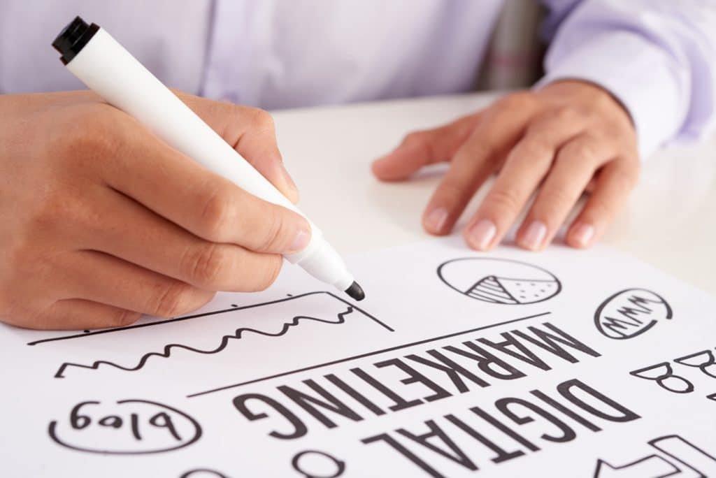 Crop hands making notes on digital marketing scheme